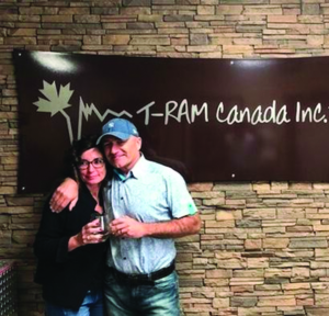 Man and woman standing in front of a stone wall with a T-Ram Canada Inc. business sign on the wall behind them