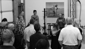 Black and white photograph from a training course where a speaker is demonstrating well plungers to a group