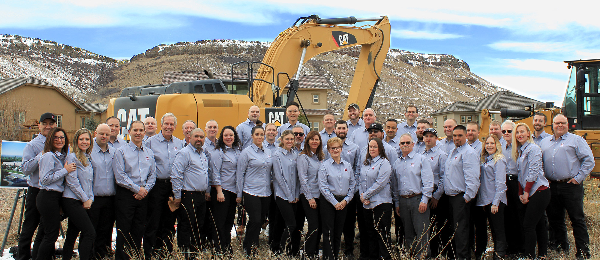 Well Master group photo of the employees wearing matching well master button up shirts and standing in front of a construction crane with the mountains behind them